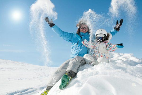 Father and daughter having fun on ski holiday